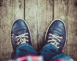 blue shoes on wooden planked floor from above