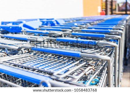 83f8639cbbd Blue shopping carts outside by store with closeup of many rows by parking  lot  1058483768