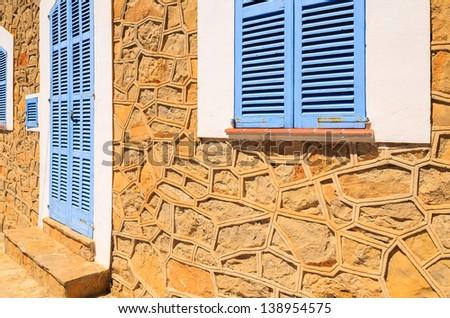 Blue shutters door traditional house stone facade, Sant Elm, Majorca island, Spain
