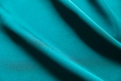 Blue silk drapery and upholstery fabric from the courtyard. Blue satin, silky fabric, wave, draperies. Beautiful textile backdrop. Close-up. Top view