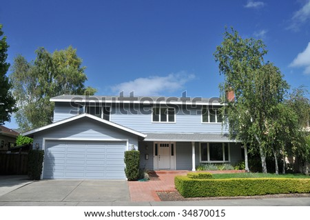 Blue single family house with trees and shrubs in front
