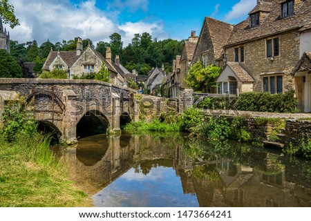 Blue skies and reflections in the picturesque Cotswold village of Castle Combe.