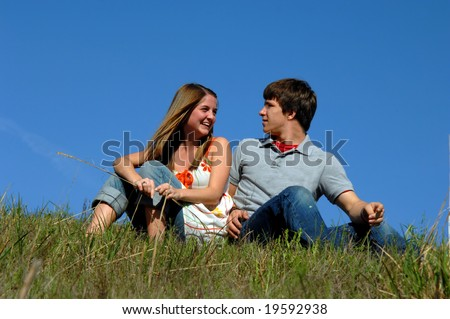 Blue skies frame young teen couple.  They are sitting on a grassy hill side-by side.