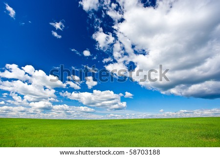 blue skies with clouds above green grass land