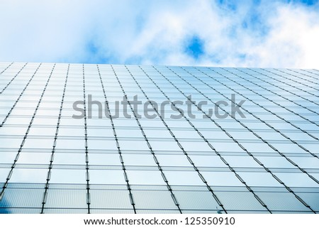 Blue sky and business skyscrapers with wall fully made of glass mirroring sky and clouds