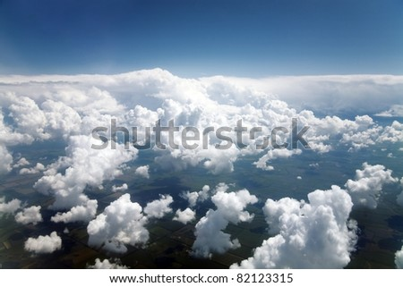 blue sky and clouds and fields visible through them from a plane window