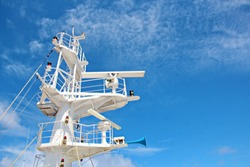 Blue sky and clouds in the open ocean. Views of the ship's mast and antennas on the navigation deck.