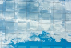 blue sky and clouds reflected in windows of modern office building