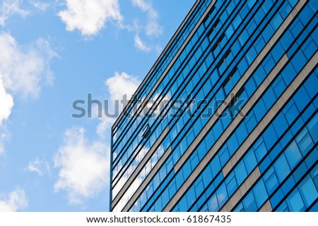 blue sky and clouds reflecting in the glass of an office building