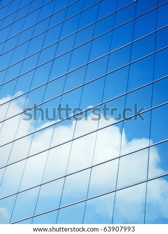 Blue sky and clouds reflecting on a building with mirrored glass