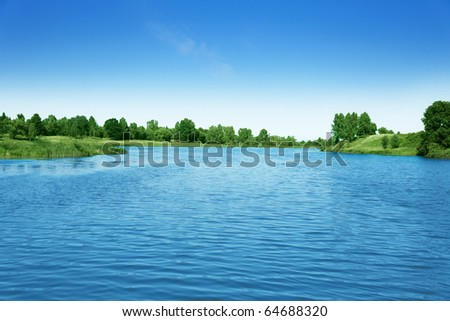 Blue sky and green trees over lake.