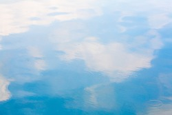Blue sky and white cloud reflect on the water in a bright day look like impressionist painting, Water reflection abstract background concept