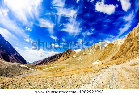Blue sky and white clouds over a mountain valley. Mountain blue sky landscape. Mountain sky landscape