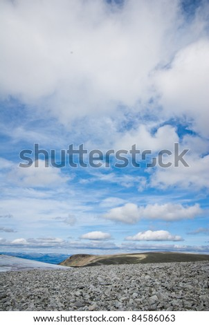 blue sky and white clouds over rocky landscape in Norway