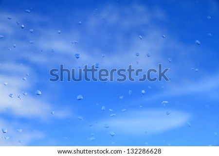 Blue sky and white clouds seen through a rain splashed window