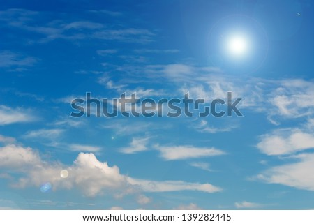 blue sky and white clouds with lens flare