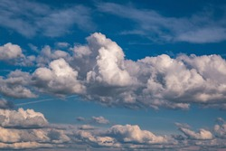 Blue sky background with big white tiny stratus cirrus striped clouds
