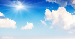 Blue sky background with clouds and sun