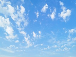 Blue sky background with scattered white clouds