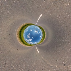 blue sky ball in middle of swirling asphalt road or field. Inversion of tiny planet transformation of spherical panorama 360 degrees. Spherical abstract view. Curvature of space.