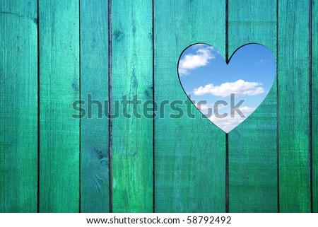 blue sky hole in a wooden wall background - stock photo