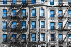 Blue sky reflected in the windows of a black and white building in New York City