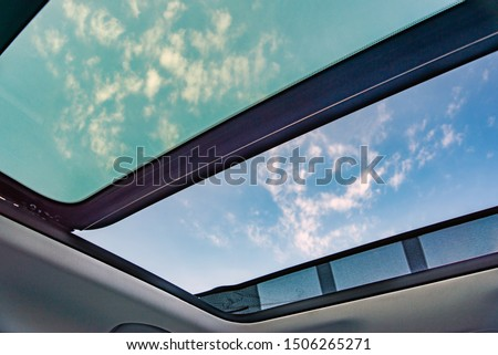 Blue sky through an open car sunroof , view from the passenger compartment,open sunroof look up to sky. Foto stock ©