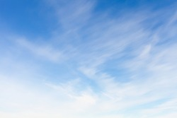 Blue sky with blurred windy clouds at daytime. Natural background photo texture