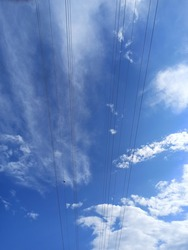 Blue sky with clouds and electric wires, a bird is on wire