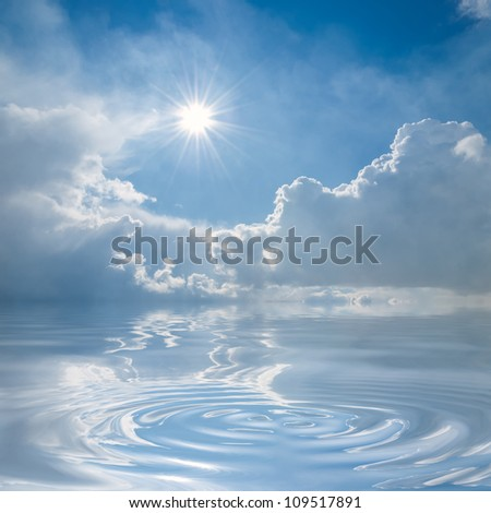 Blue sky with clouds and sun reflection in water with waves