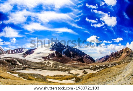 Blue sky with clouds over a mountain peak. Mountain sky landscape. Blue sky in mountains