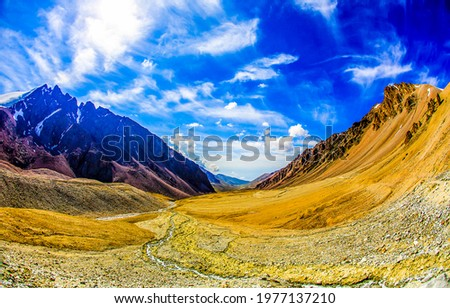 Blue sky with clouds over a mountain valley. Beautiful mountain valley. Valley in mountains. Mountain blue sky clouds