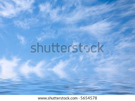 blue sky with fleecy clouds and reflection in smooth water surface