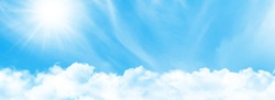 Blue sky with light clouds and bright sun. Wide summer sky backdrop