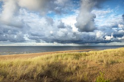 Blue sky with lots of cumulus clouds above the Baltic sea after thunderstorm at sunset. Sandy beach, dune grass close-up. Idyllic landscape. Warm evening sunlight. Travel destinations, eco tourism