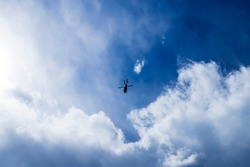 Blue sky with small helicopter flying into a thundercloud.