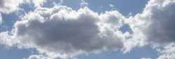blue sky with white clouds backlit by sunlight. Fluffy cumulus clouds float across the clear sky