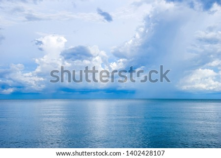 Blue sky with white clouds/ natural landscapes over blue sea and reflected in the water surface with small waves. #1402428107