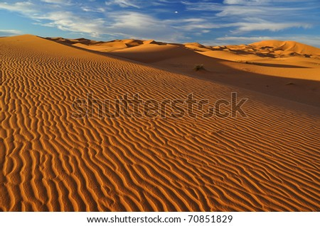 blue sky with white clouds over sand dunes in sahara desert