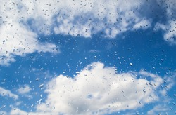 Blue sky with white clouds through the window with drops after rain