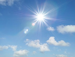Blue sky with white fluffy clouds and sun reflection. Sunny background. Sun appear directly above Thailand. The afternoon summer sun shines on a beautiful sky with clouds. Hot weather, summer season.
