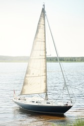 Blue sloop rigged yacht anchored to the sandy shore (beach overgrown with grass). Sailing in Sweden, Europe. Nature, summer vacations, recreation, cruise, sport, transportation. Aerial view