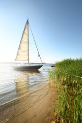 Blue sloop rigged yacht anchored to the sandy shore (beach overgrown with grass). Sailing in Sweden, Europe. Nature, summer vacations, recreation, cruise, sport, transportation, ecotourism
