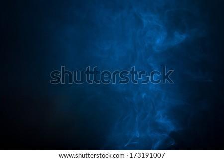 Blue smoke over black studio background