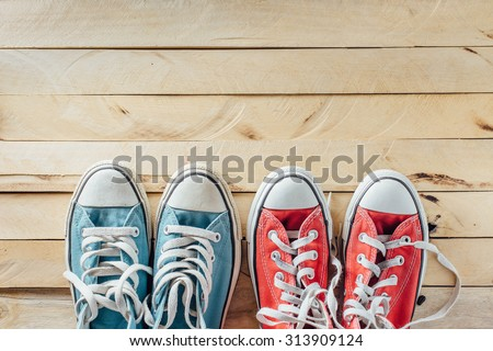 Shutterstock blue sneakers and red sneaker on wooden floor