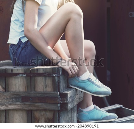 Blue sneakers on girl legs on the grunge background Close up
