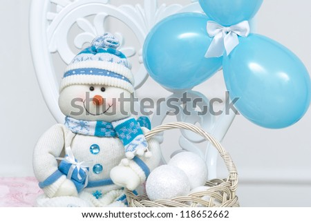 Blue snowman decoration for New Year with balloons sittings on a vintage chair