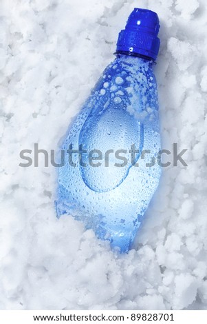 Blue soda bottle in crushed ice with back light