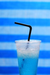 Blue soda in plastic cup with straw on stripe background.