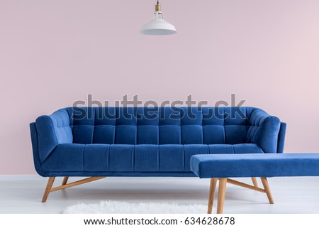 Blue sofa and bench in pink modest apartment #634628678